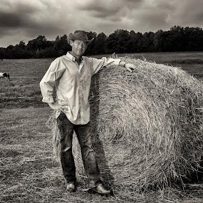 Dan Profitt down On the Farm by George Holt - People Portraits of Men ( farm, cowboy boots, cowboy hat, cowboy, sepia, hay bail, horse, hay, cloudy, musician, boots, hat )