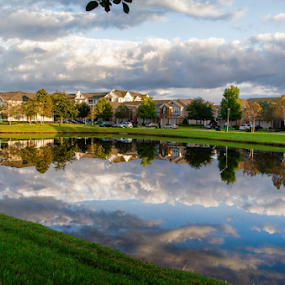 Reflections by Kati Garner - Landscapes Cloud Formations ( water, townhouses, grass, reflections, pond )