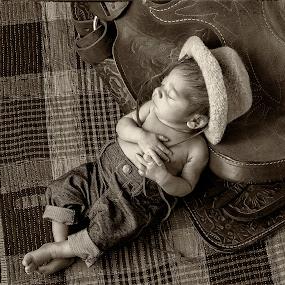 Newborn Cowboy by George Holt - Babies & Children Child Portraits ( sepia, cowboy, black and white, infant, male, sadle, cute, boy, newborn, hat )