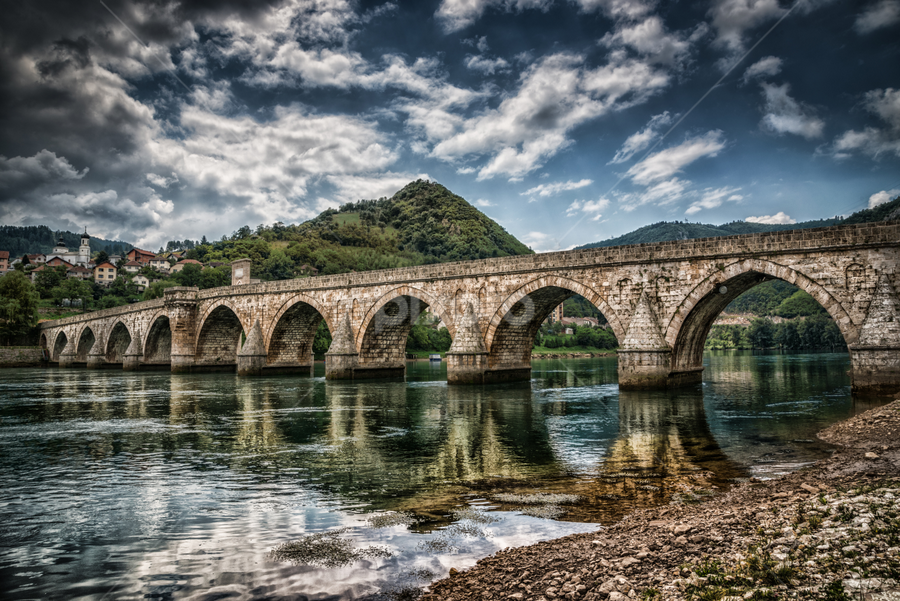 Bridge on Drina by Dobrinovphotography Dobrinov - Buildings & Architecture Bridges & Suspended Structures ( drina, old, europe, mountain, famous place, arch, ivo, stone, united nations educational, architecture, visegrad, bosnia and hercegovina, traditional culture, aging process, andric, style, restoring, travel locations, ottoman empire, social history, historic world event, journey, landscaped, sokolovic, recovery, riverbank, serbia and montenegro, history, architecture and buildings, urban scene, islam, serbia, cuprija, column, scientific and cultural organization, summer, day, bridge, built structure, waterfront, river,  )