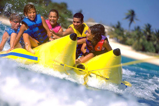family-fun-in-banana-boat-Aruba - A family takes a raft ride on a banana boat on Aruba.