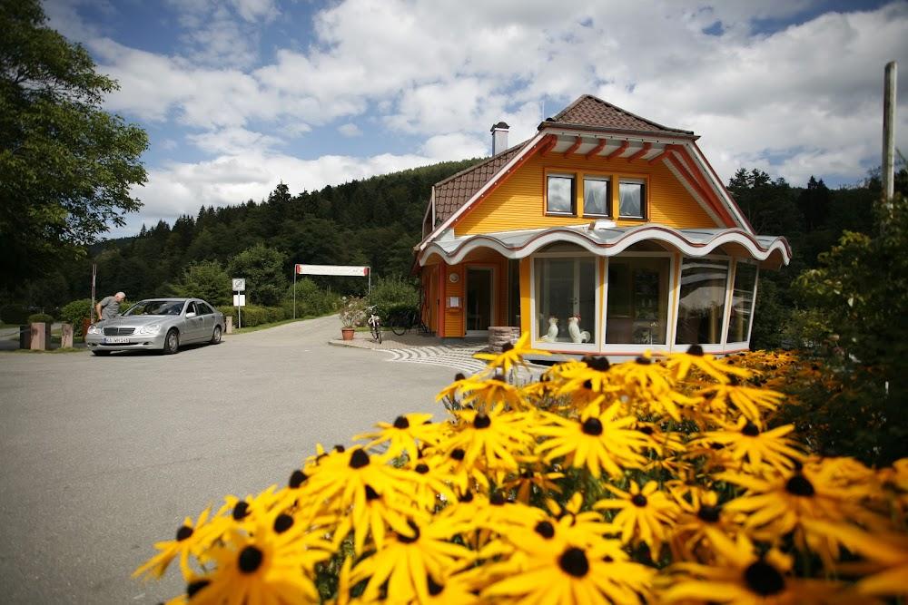 Du siehst gelbe Blumen und die Touristinformation des Kleinenzhofes, ein orangefarbenes Haus .