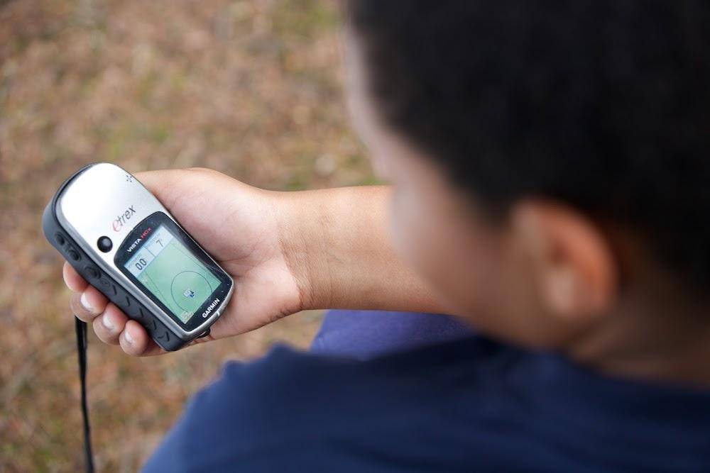 Du siehst einen Jungen, der ein GPS Gerät in der Hand hält.