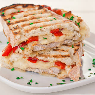 Marinated Pork Sandwich with Rosemary Aioli, Mozzarella Cheese and Roasted Red Peppers.