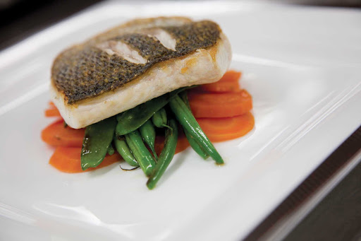 Cunard-Queen-Mary-2-dining-entree - A fish entrée with snap peas and carrots served at Queen Mary 2's Todd English restaurant, designed by renowned chef Todd English.
