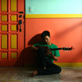 young musician by Jun Pinzon - People Musicians & Entertainers ( music, orange, home, musical, male, play, door, youth, house, instrument, young, kid, asian, playing, sit, sitting, floor, blue, empty, acoustic, musician, guitar, boy, wall )